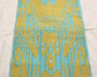 Uzbek turquoise-yellow silk ikat fabric. Traditional woven fabric Adras