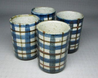 set of four pottery cups , maybe juice glass size ( sake ?  ) not marked Otagiri plaid blue brown stoneware
