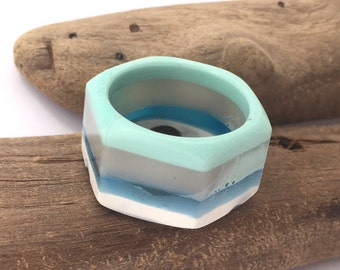 Eco-resin industrial hex nut ring in freestyle abstract layers of mint, grey, translucent blue, white and black.