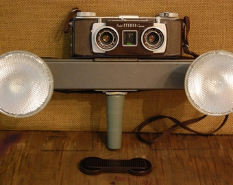 Vintage Kodak Stereo Camera with hand held dual light bar, neck strap and lens cover, both in excellent condition with all controls working