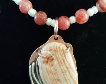 Rhodochrosite necklace with a copper and silver pendant that has a fragment of a shell as a focal point