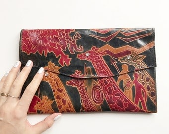 Flat leather envelope clutch with giraffes.