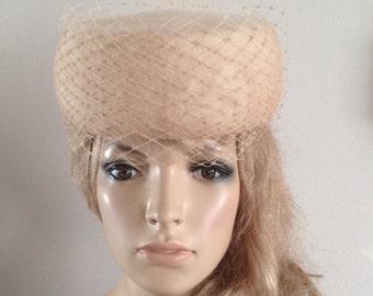 Beige wool felt pillbox hat adorned with ton-sur-ton merry widow veiling