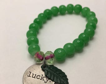 Emerald Green beaded flexible bracelet with a Round Antiqued Silver LUCKY charm & Forest Green Metal Leaf.