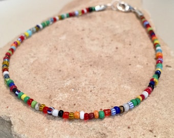 Multicolored seed bead ankle bracelet made with African Christmas beads, flower stamped tube beads and a sterling silver trigger clasp