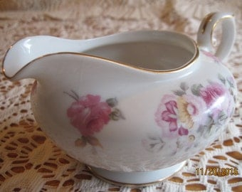 white porcelain creamer, marked Grace China, made in occupied japan adorned with floral design and gold trim