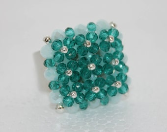 Maxi ring of stones and crystals in shades of green and light blue.