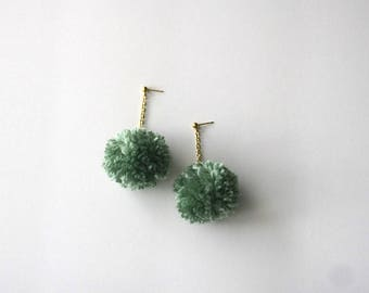 Pom-pom drop earrings dangling on gold chain and gold stud in heathered aqua blue