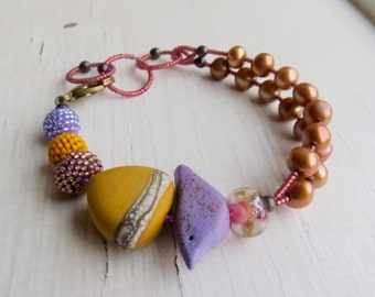 Honeydukes - handmade freshwater pearl and artisan bead bracelet in saffron yellow, lilac and topaz with bird detail - Songbead, UK