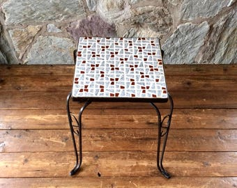 Elegant mid-century side table or plant stand with ceramic mosaic top in pale blue and brown with black iron frame and legs. 60s style.