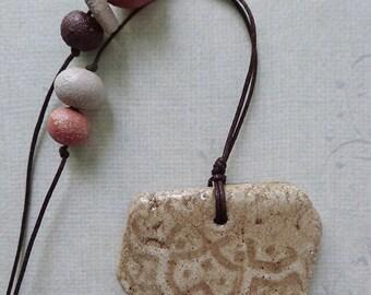 Beige ceramic handmade pendant, necklace with imprint.