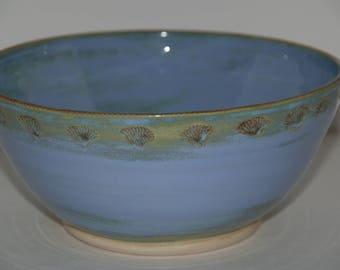 Large handmade blue pottery bowl with shells and decoration
