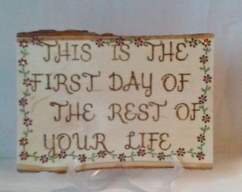 Wood burned painted and embellished plaque with purple flowers and inspirational saying This is the First Day of the Rest of your Life.