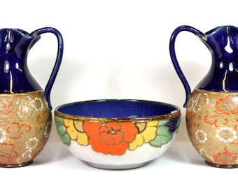 A tube lined stoneware bowl and a pair of Doulton stoneware ewers, H. 22cm, bowl Dia. 20cm.