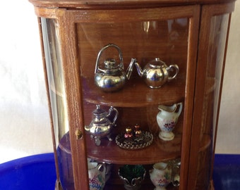 Miniature Hutch with 11 pieces of assorted serving dishes and pitchers.