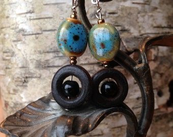 Painted clay, silver and wood bead drop earrings with lever back closure.
