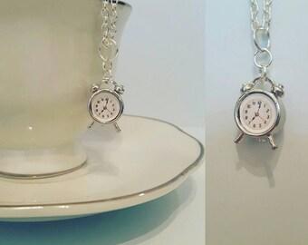 Super cute miniature silver alarm clock charm necklace. Miniature silver clock on a silver plated chain.