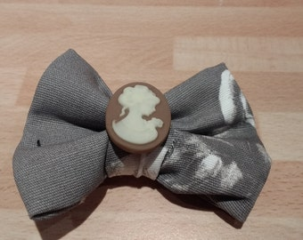 Clip on Hair-Bow Periodic Style  With A Cameo Embellishment And A Black Floral Vintage Fabric.