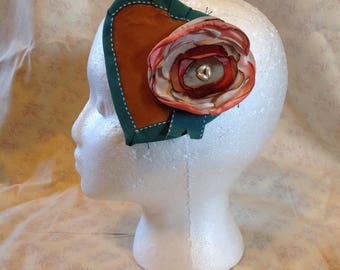 soft brown leather heart shaped hair decoration with green ribbon and flower embellishment.