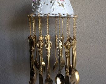 Wind Chime, gold colored silverware on ceramic top with flowers.
