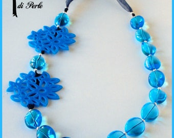 Blue glass necklace and flowers in plexiglass