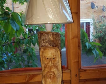 Face carved tree trunk lamp