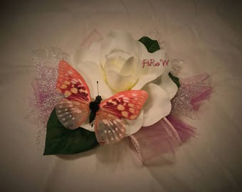 Gardenia fascinator with pink butterfly.