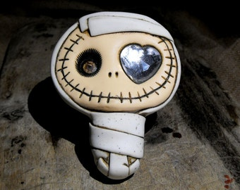 Happy baby mummy brooch in dirty white. Creepy and cute skull with a shiny heart his eye.
