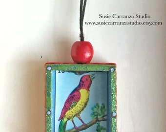 Nicho Ornament - El Pajaro. Blue and Gold with Red Wood Bead. Colorful glittery accents, red rick rack ribbon. Loteria art.