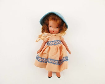 A 'Nancy Ann' Story Book Doll - Bisque, Mid 40s Doll - Peach Dress With Teal Trim and Teal Hat With Pink Ribbon - Frozen Leg