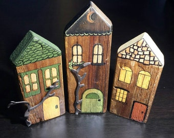 3 handpainted houses made from very old barn wood. Vintage metal odds as branches.