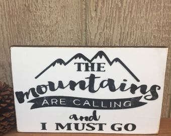 The Mountains Are Calling And I Must Go - Handmade frame less sign, distressed white background, mountain silhouette and font in black  (WH)