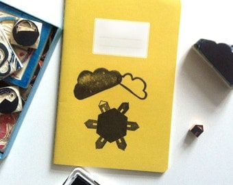 """1 mustard-yellow notebook with lovingly illustrated cover """"Better World at home"""""""