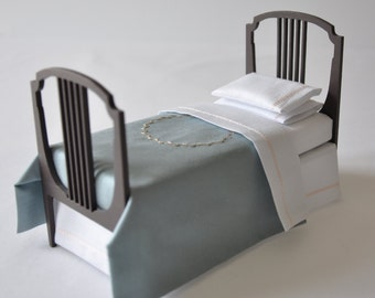 Single bed with blue silk bedspread