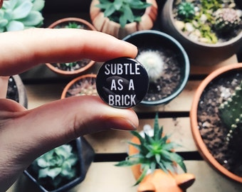 "Subtle As A Brick 1"" Pinback Button (Brand New, Taking Back Sunday, emo)"