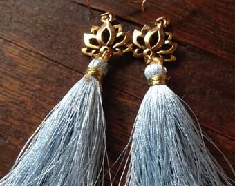 Frost blue silk tassel earring on a silver lotus blossom pendant.