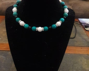 A claspless choker in green-turquoise, white, and black.