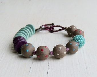 Polka - handmade chocolate brown, purple and mint green ceramic and glass artisan bead bracelet - Songbead, UK - narrative jewellery