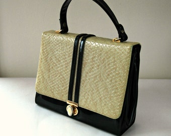Black patent handbag with textured faux snake skin and front flap.