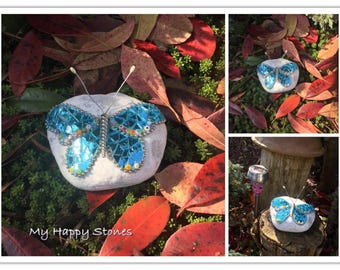 Blue butterfly of mirror glass on white stone.