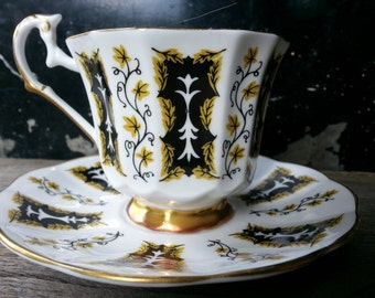 Vintage Sandringham footed tea cup and saucer with crisp white background and unique black and gold pattern