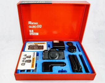 Pentax Auto 110 Submini SLR with three (3) lenses, flash and manual, in original box
