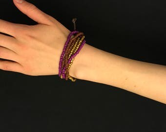 Beaded bracelet. Gold, purple and brown colored beads.