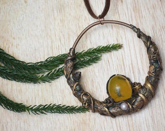 Copper pendant with brass-colored clay vines and amber eye. It's BOOKED!
