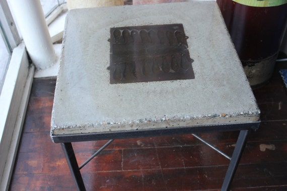 coffee table, polished concrete on steel base with antique fishing weight foundry mold casted in