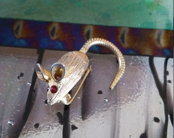 Tiny gold mouse pin with red eyes
