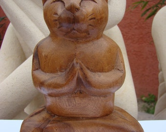 Cat zen wisdom namaste in position of yoga meditation in wood carved
