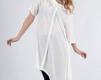 Oversize, white asymmetrical shirt with 3/4 sleeve and elongated back, designed to stretch the silhouette