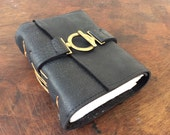 Elegant black reclaimed leather diary with handmade paper and unique latch