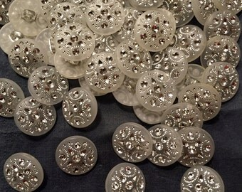 One inch in diameter  fancy frosted white buttons with stones. Shank back  4 pieces
